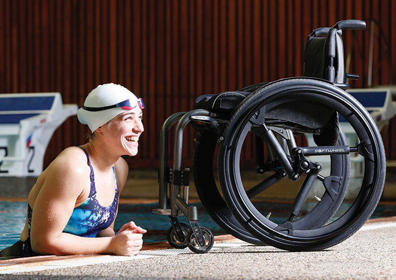 An image of a woman half‐way out of a swimming pool. Her wheelchair is in front of her. It uses a pair of NuMotion SoftWheels.